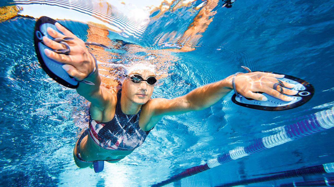Schwimmerin trainiert mit Handpaddles