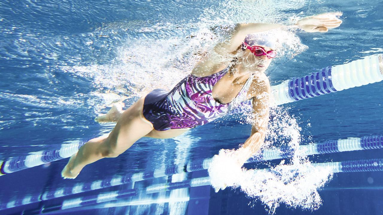 Unterwasseraufnahme einer Schwimmerin in einem Sportschwimmbecken.