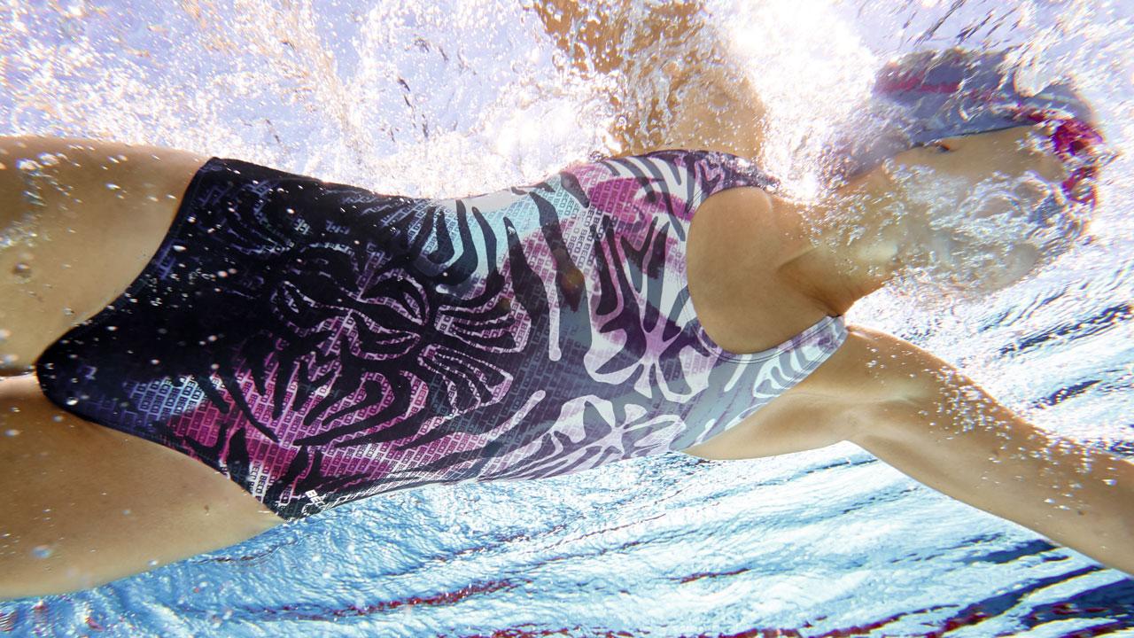 Eine Schwimmerin gleitet durchs Schwimmbecken