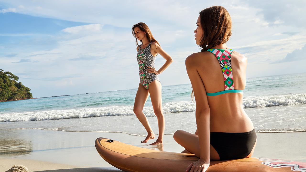 Zwei Frauen präsentieren Bademode an einem tropischen Strand