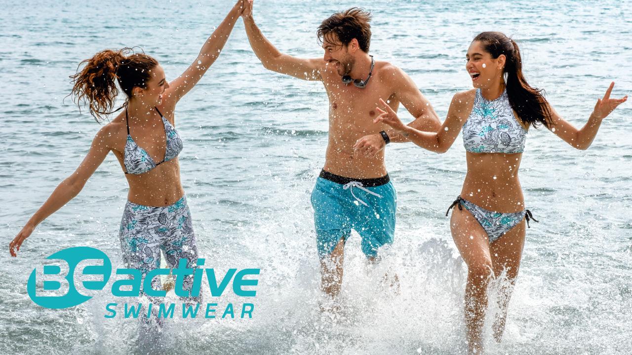 Fröhliche junge Menschen laufen durchs Wasser