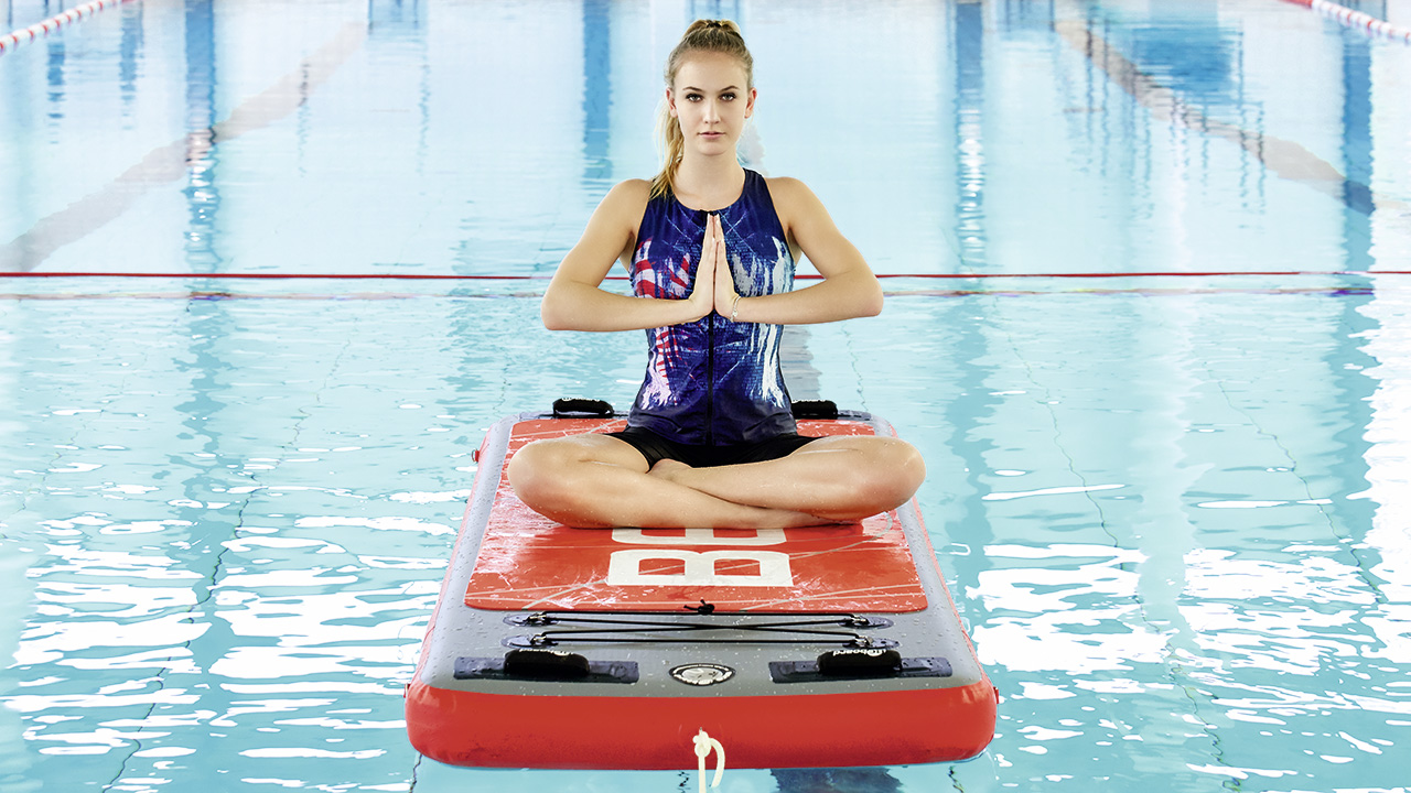 Woman practises yoga on a swimming board