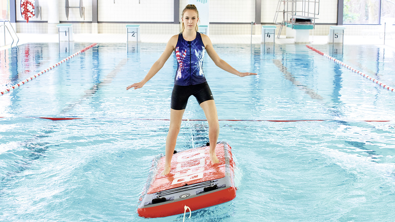 Woman trains in an indoor pool on a floating board