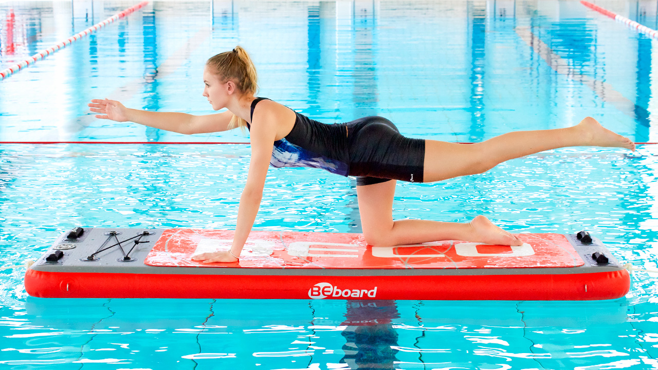 Sportswoman practices yoga on a swimming board