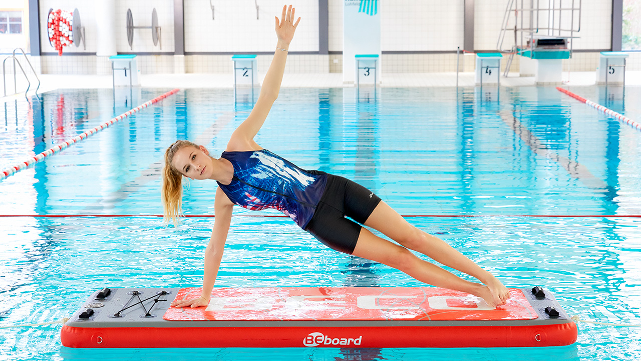 Sportswoman practices yoga on a floating board