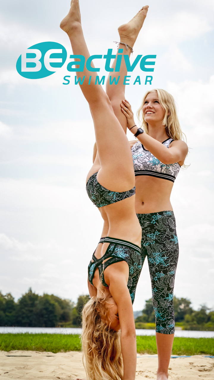 Two women perform a handstand on the beach